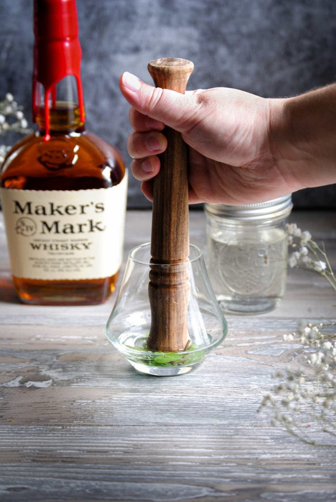 muddling simple and syrup and mint in a whiskey glass