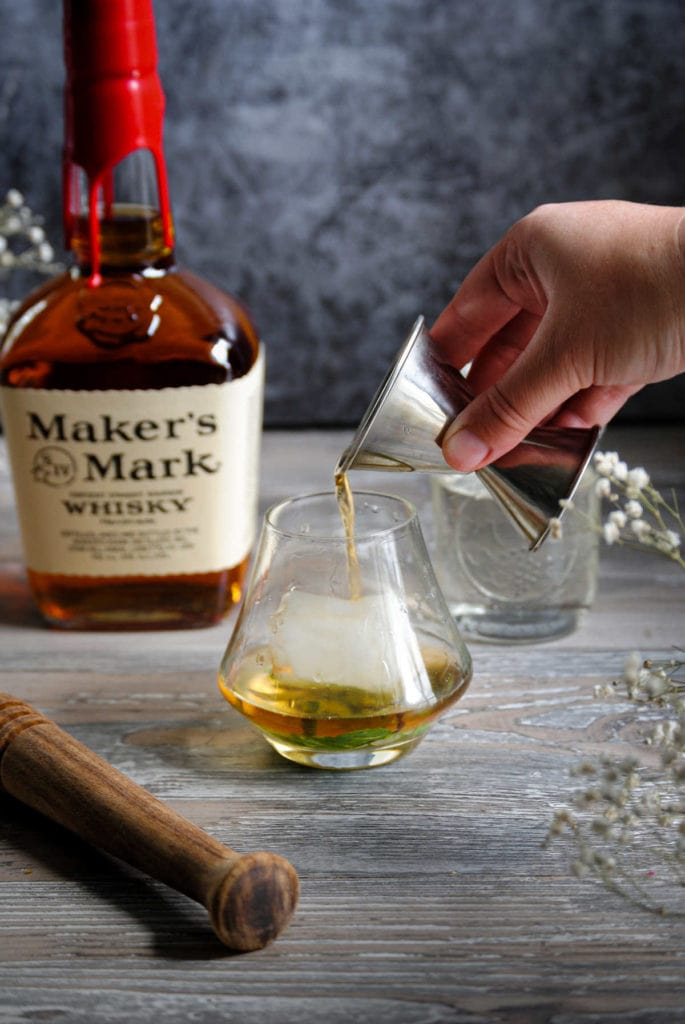 pouring bourbon over simple syrup and mint