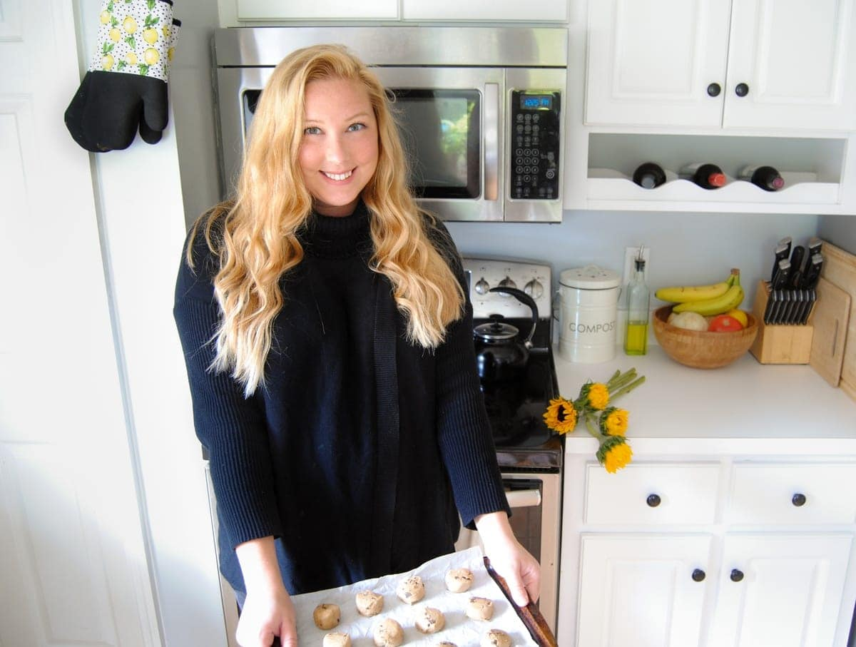 Picture of female home cook in her kitchen holding tray of cookies ready to put in the oven
