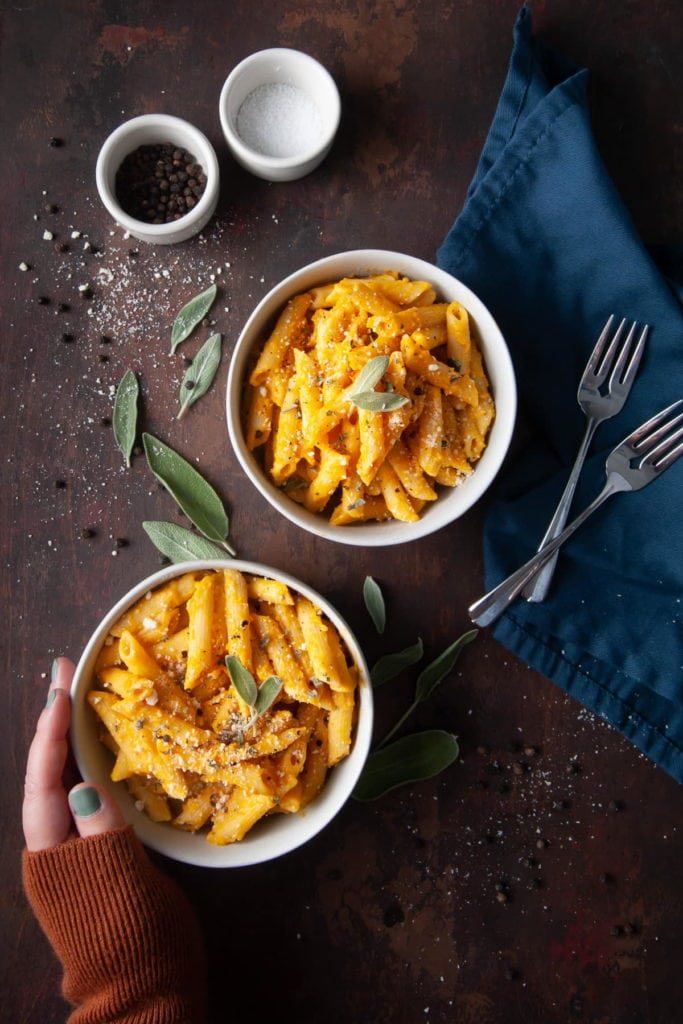 two bowls of pumpkin and sage pasta with hand on one bowl