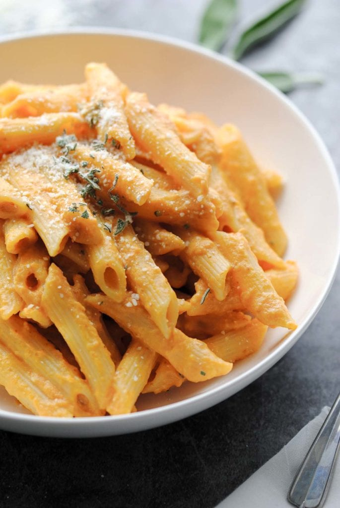 Close up of a stack of pasta in a bowl topped with parmesan and sage