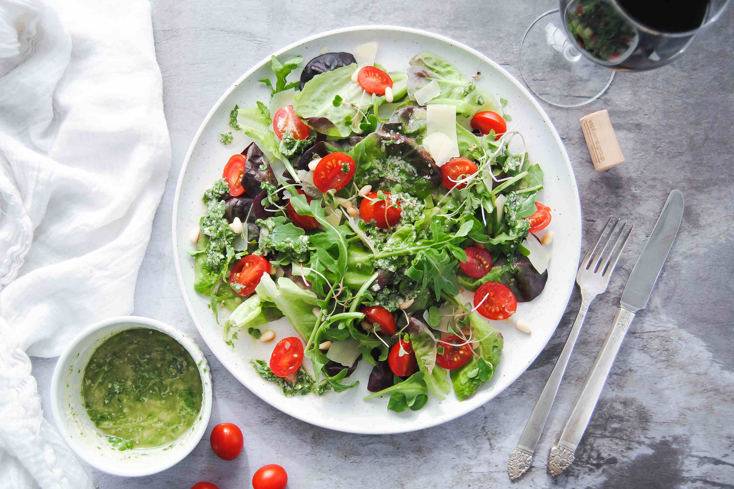 picture of green salad with tomatoes surrounded by vinaigrette and wine and utensils