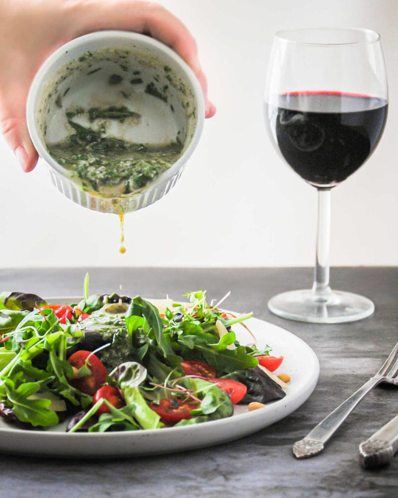 pouring pesto vinaigrette onto salad with glass of wine in the background