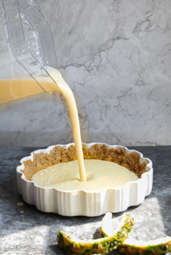 Pouring Pineapple Pie Filling into graham cracker crust