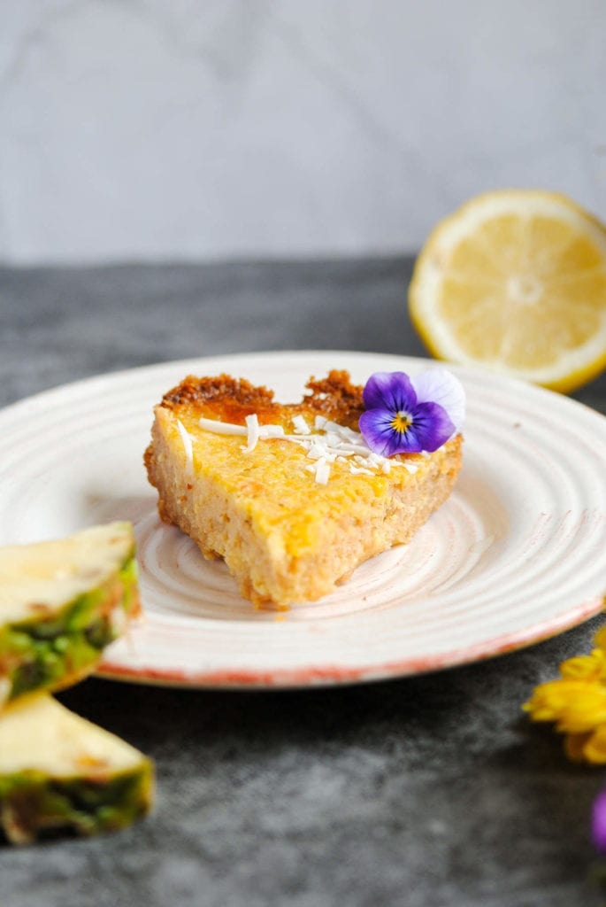 a slice of pineapple pie decorated with violas sitting on a white plate