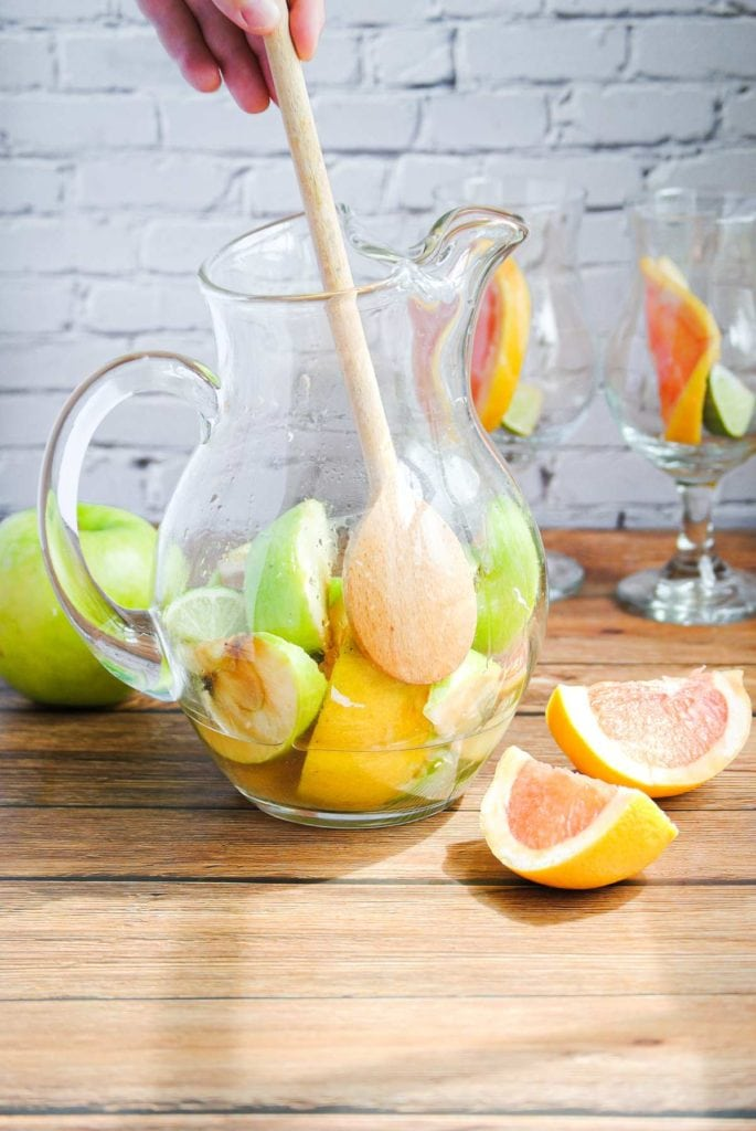 wooden spoon stirring fruit and rum inside a glass pitcher