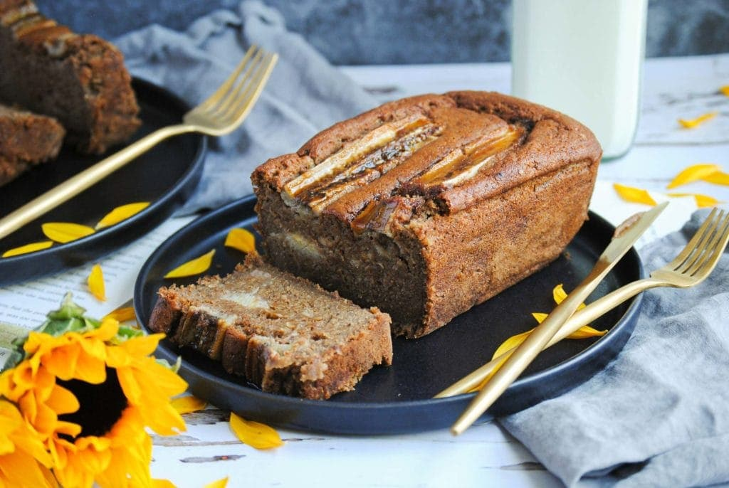 vegan banana bread on a plate with one slice cut and sunflowers
