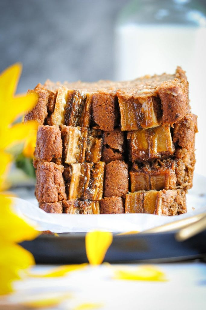 Slices of Vegan Blender Banana Bread stacked on top of each other with a sunflower