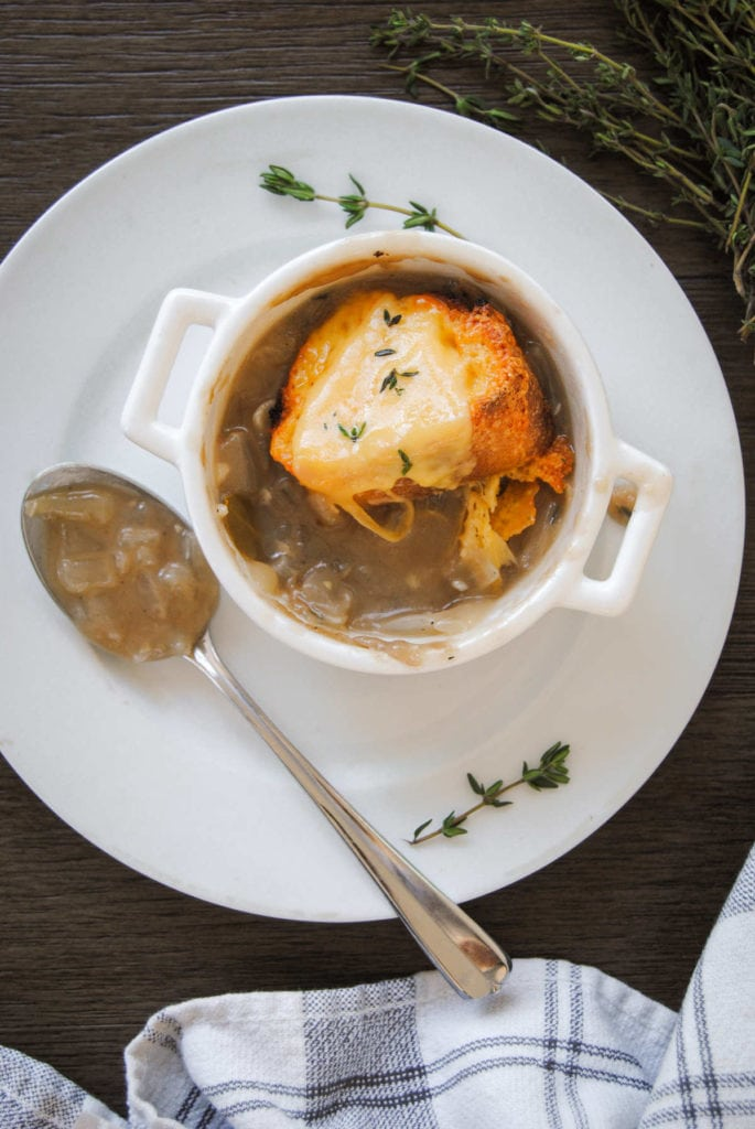 individual serving of french onion soup with spoon next to it