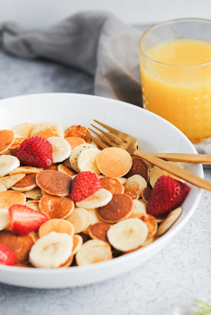 portrait of baby banana pancakes in a bowl with strawberries and gold forks