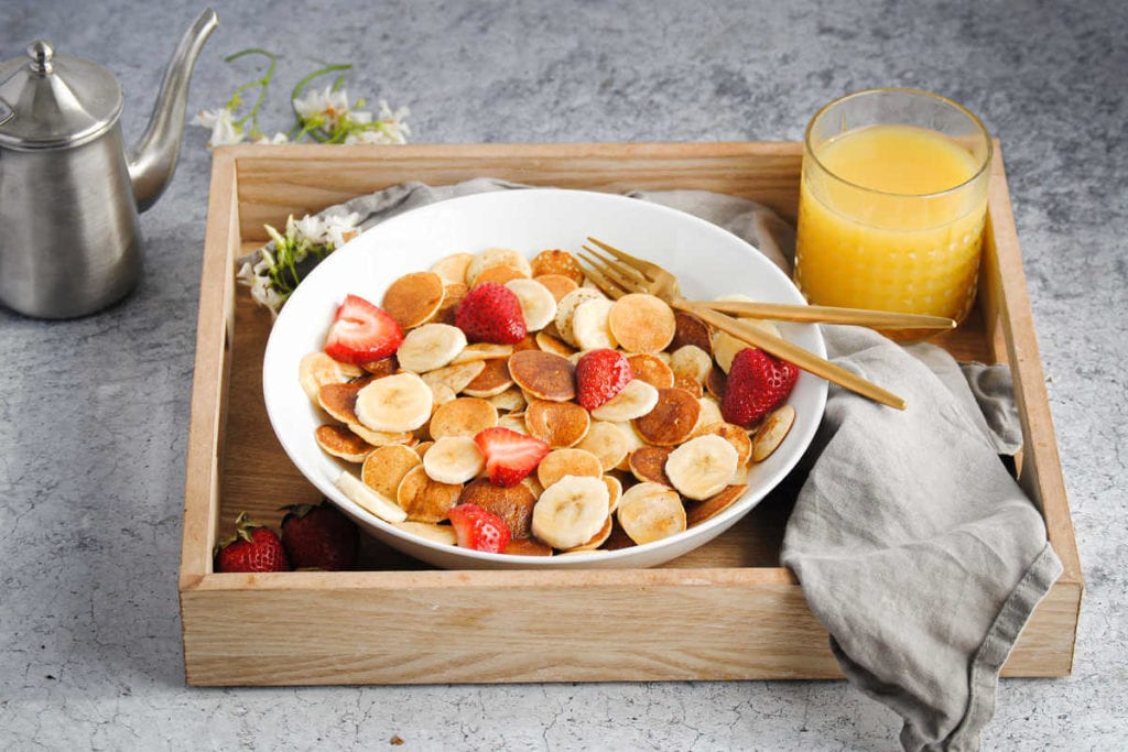 bowl of mini pancakes with strawberries on a breakfast tray with juice