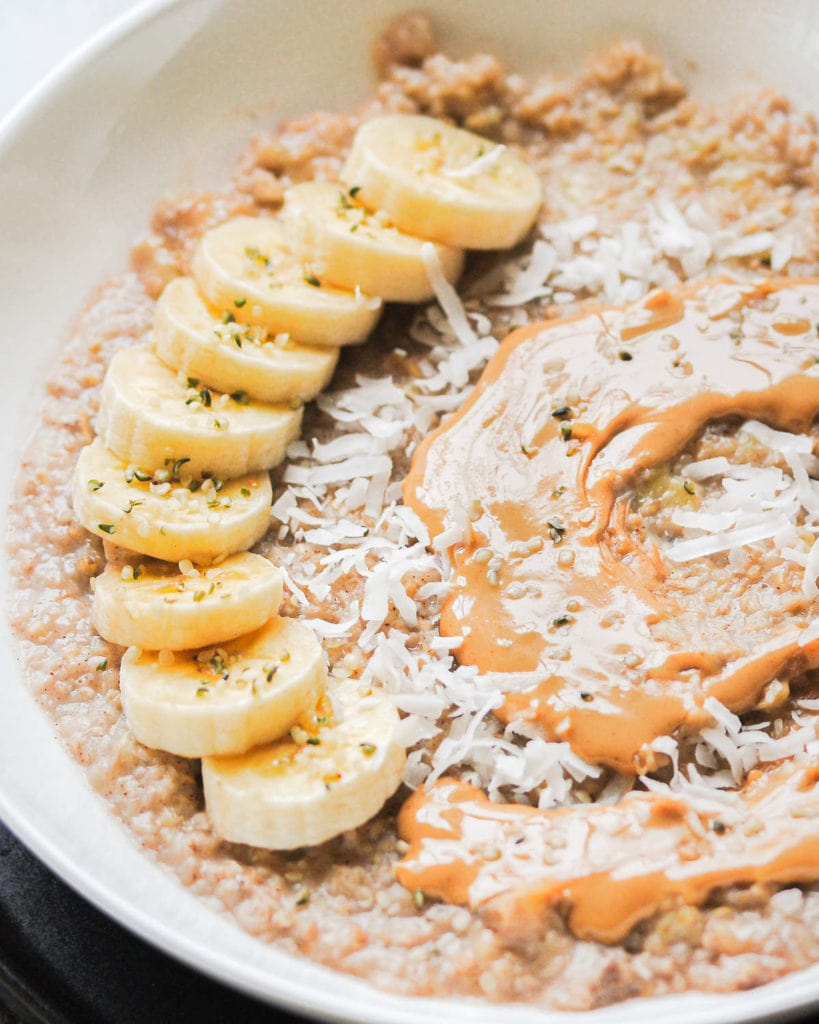 close up of porridge with sliced banana,  peanut butter and coconut flakes