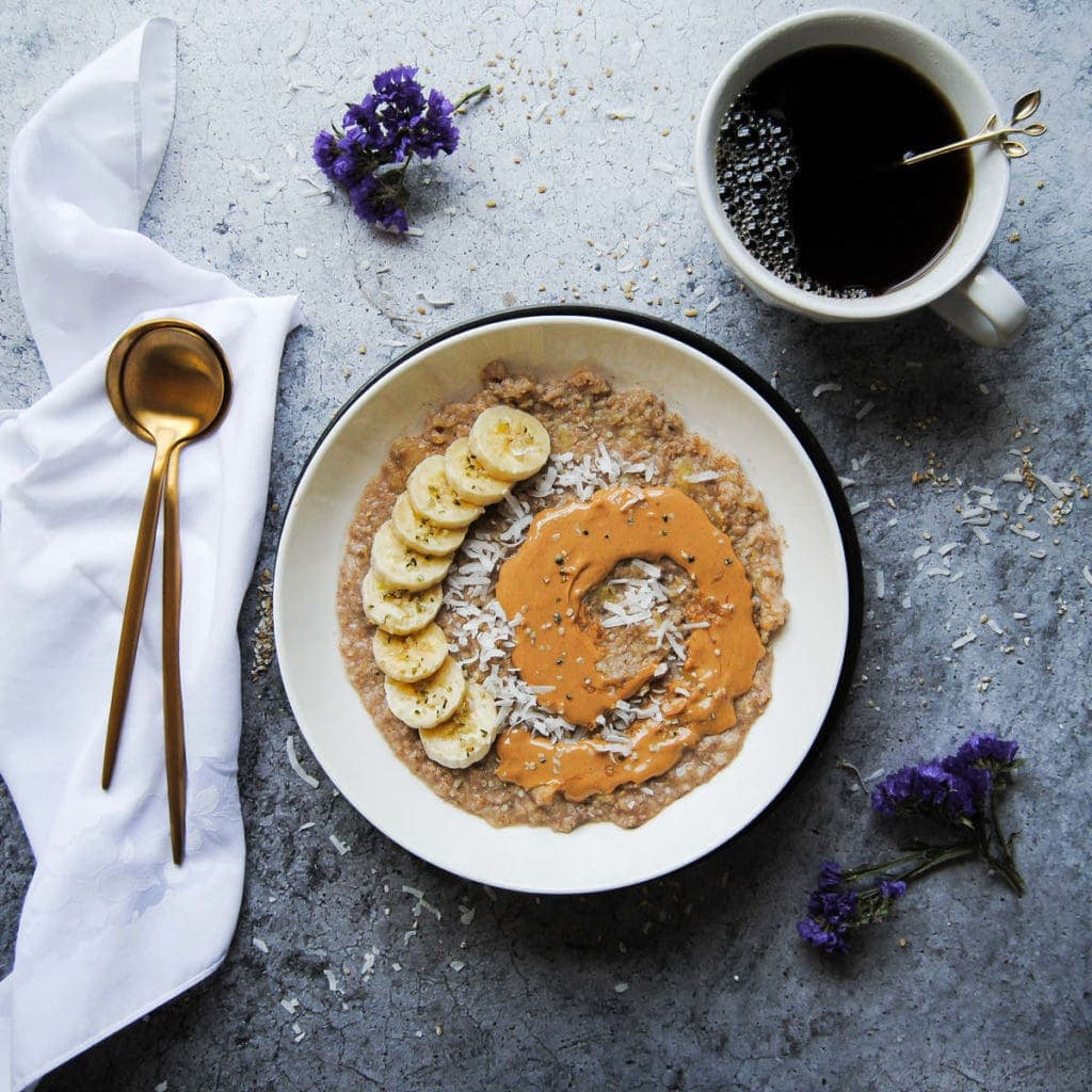 breakfast of porridge with peanut butter and bananas and cofee
