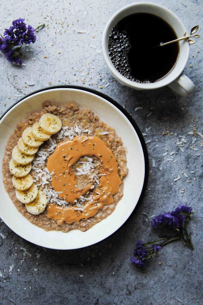 portrait of banana porridge with sliced banana, peanut butter, and coconut flakes