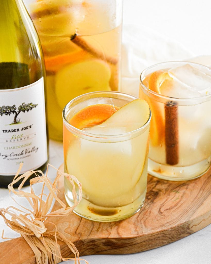 two glasses of white wine with a cinnamon stick and orange
