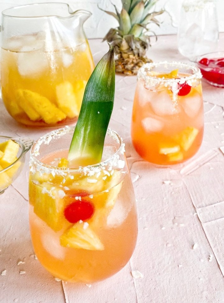 two glasses of wine with pineapple and cherry in it and pineapple leaf garnish