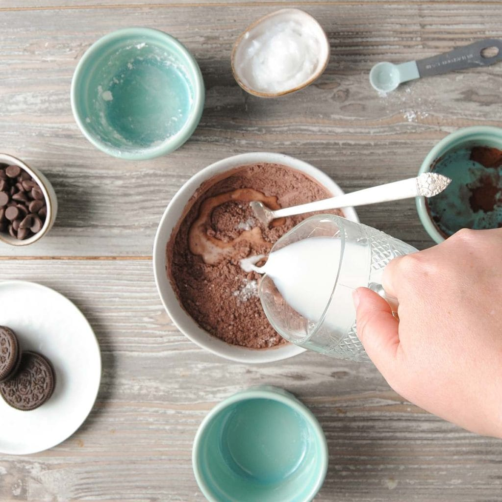 pouring milk into dry ingredients of mug cake