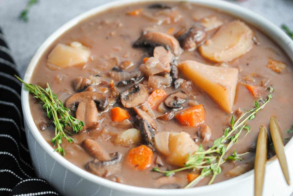 close up of serving bowl filled with stew with carrots, mushroms, and potatoes peeking out