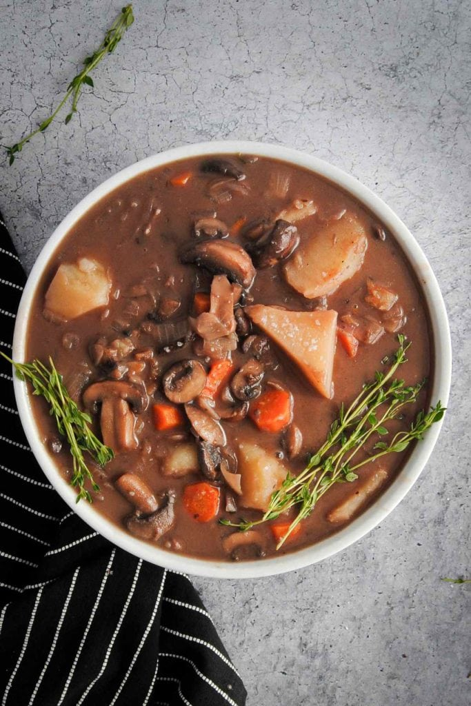 overhead shot of mushroom stew with potatoes and carrots garnished with fresh thyme
