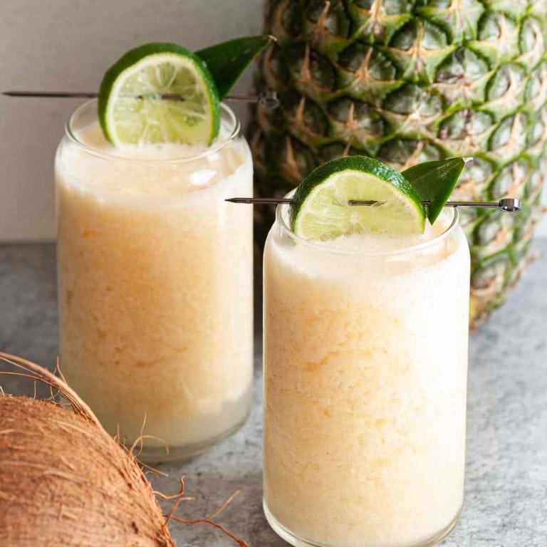 two glasses of frozen pineapple coconut margarita garnished with lime