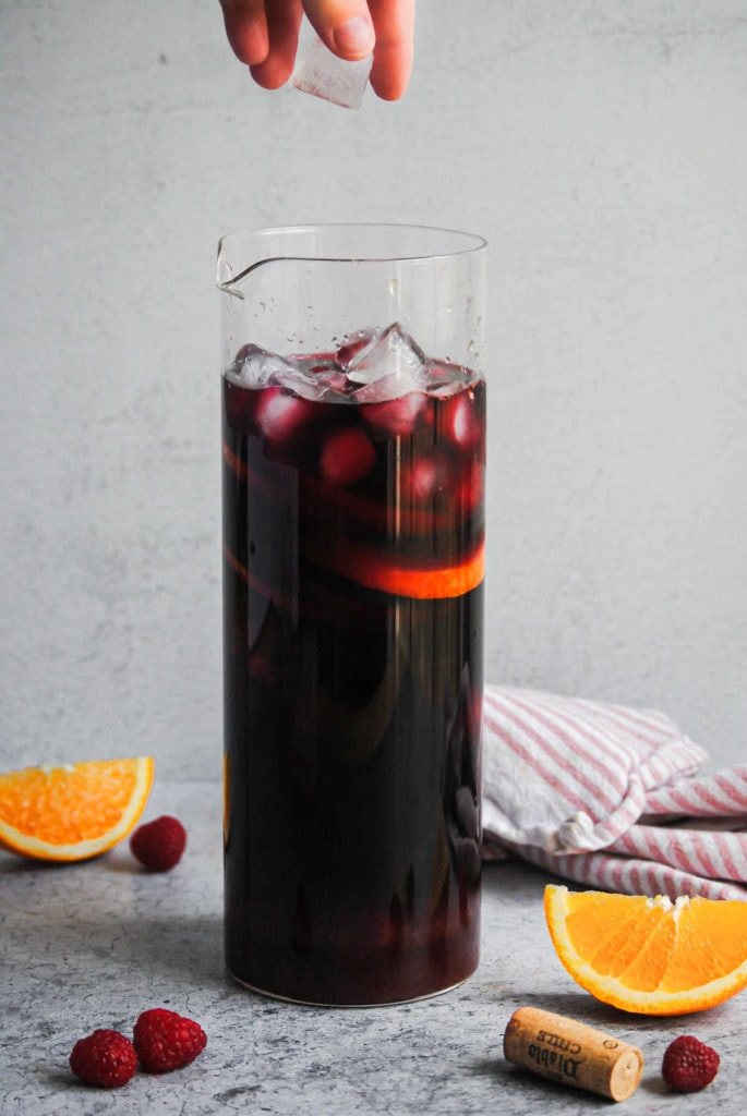 adding ice to a pitcher of raspberry sangria