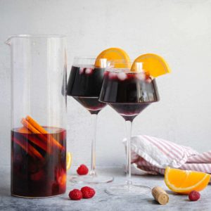 2 wine glasses full of sangria sitting next to a half empty pitcher