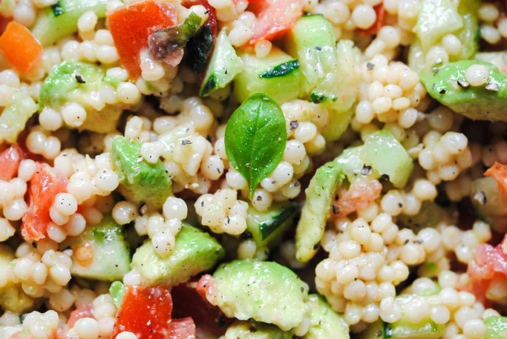super close up of pearled couscous basil avocado tomato and cucumber