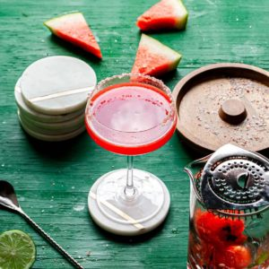 pink margarita in coupe glass with salted rim surrounded by watermelon