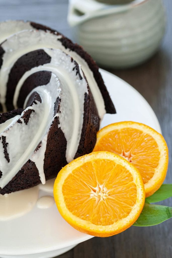 Close Up of Chocolate Bundt Cake with White Glaze and Two Slices of Orange