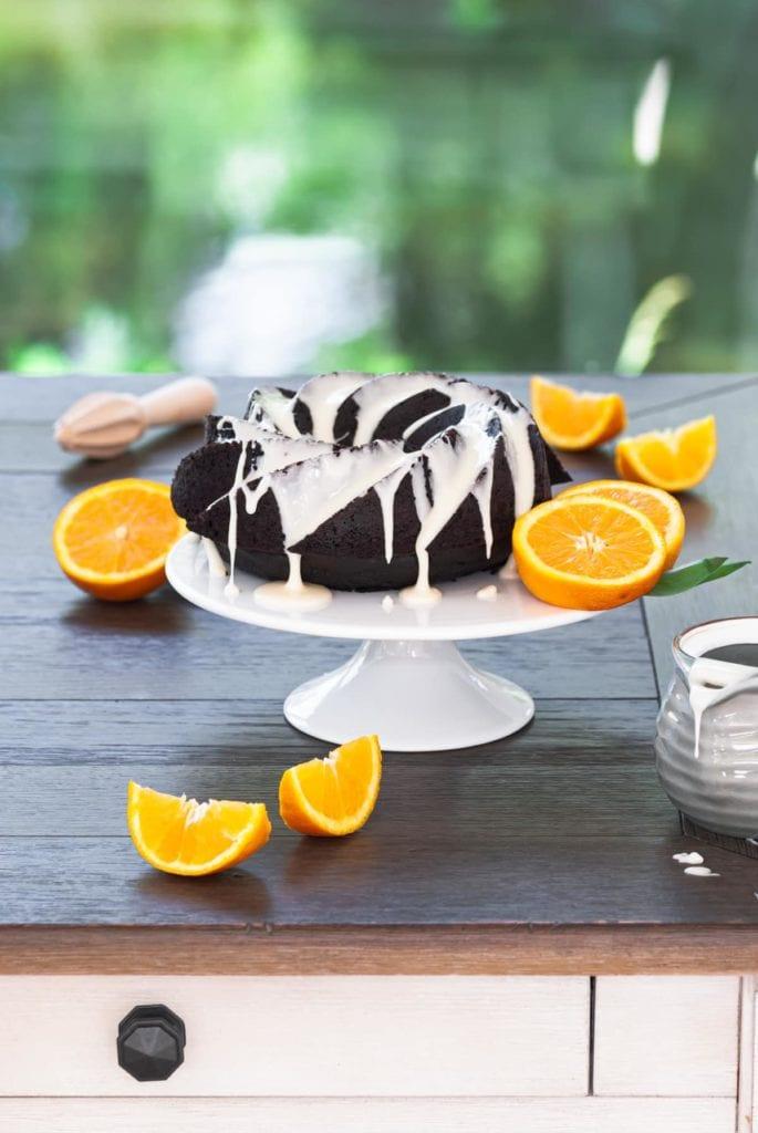 portrait of chocolate orange cake with orange glaze and surrounded by orange slices