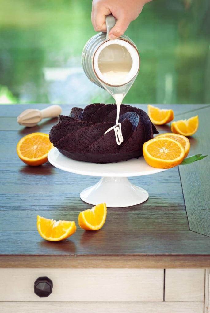 Pouring orange glaze onto chocolate bundt cake