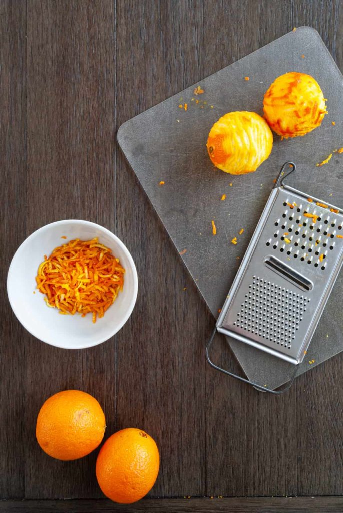 two zested oranges and bowl of zest