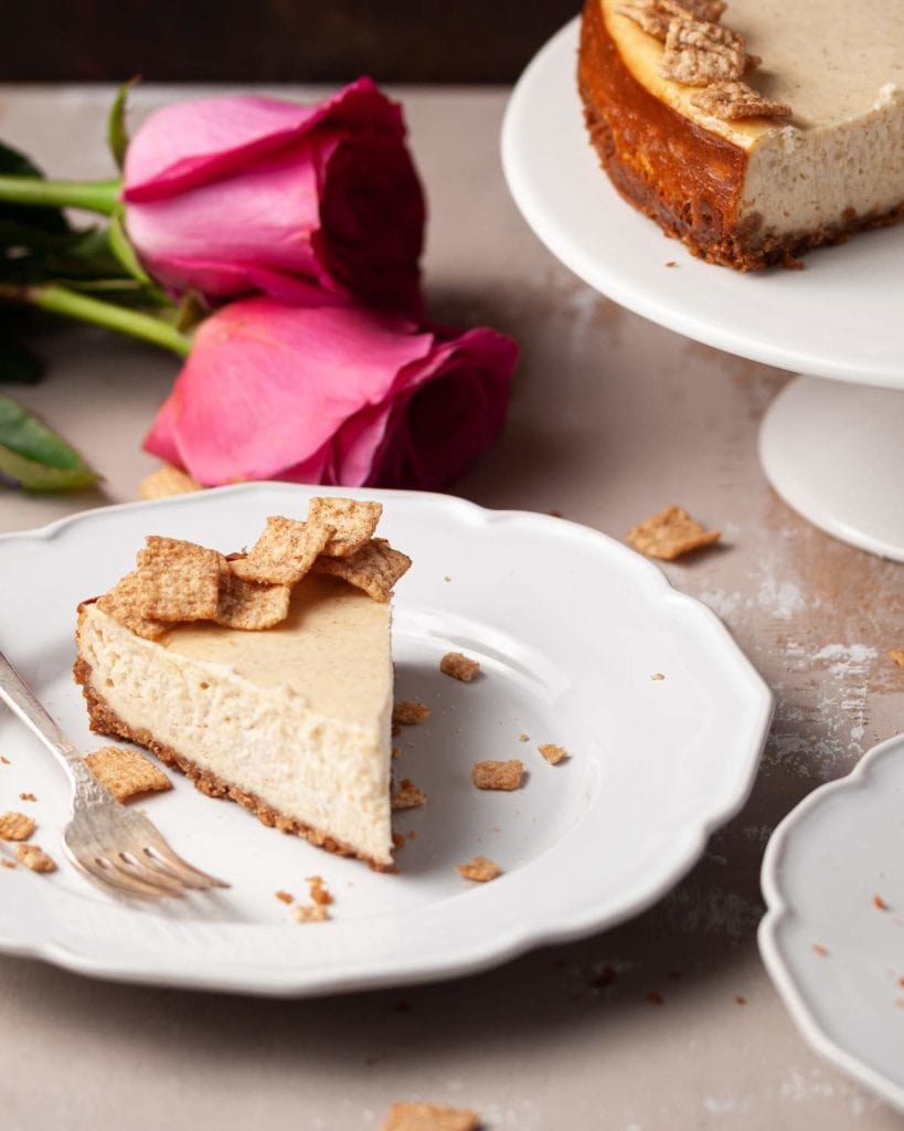 Slice of Cheesecake in front of roses and a cake stand