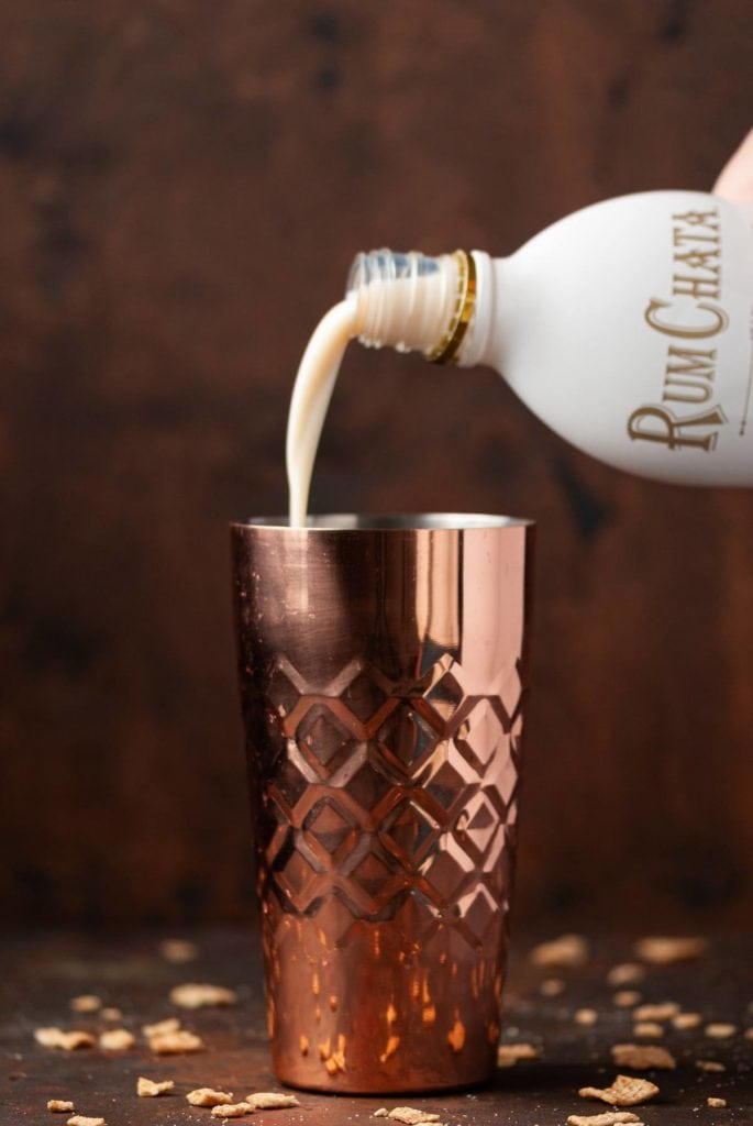 pouring rum chata into cocktail shaker