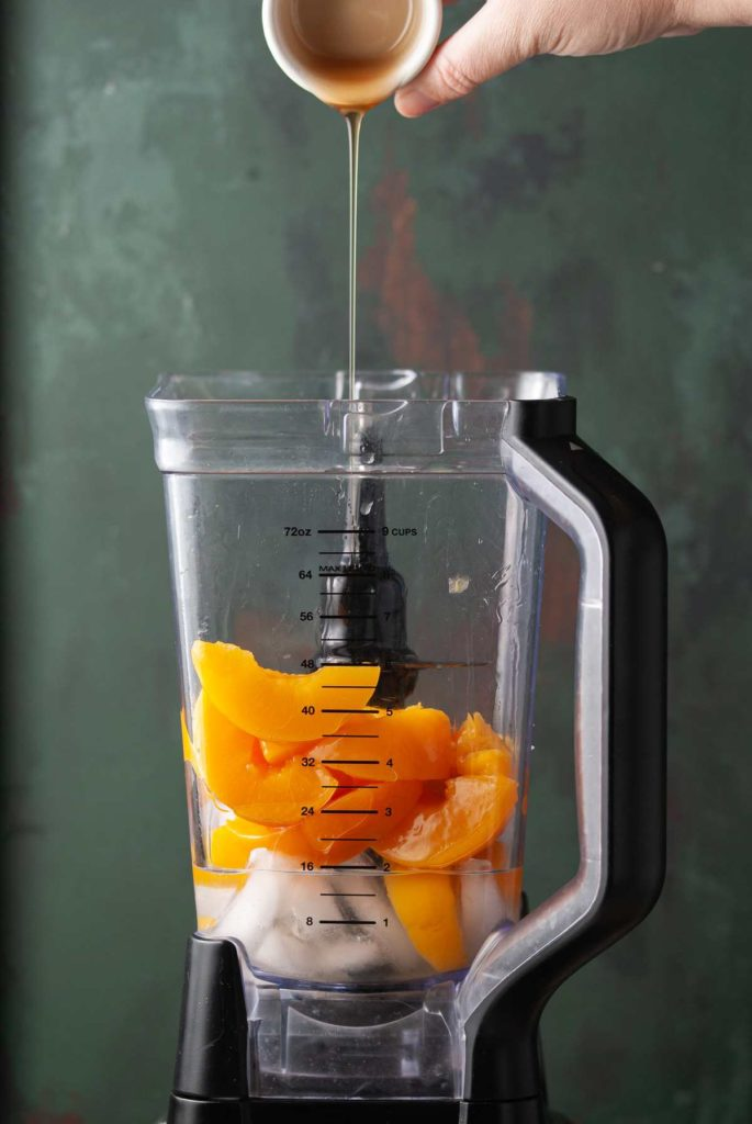 adding agave to a blender with peaches, ice, and tequila
