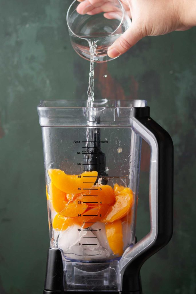 adding tequila to a blender with peaches and ice