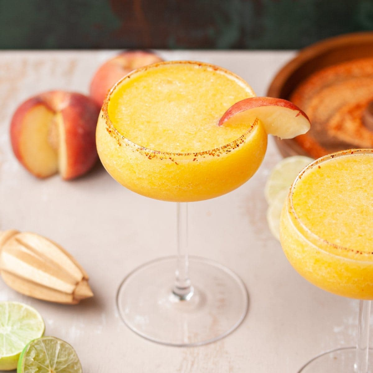frozen cocktail garnished with a slice of peach