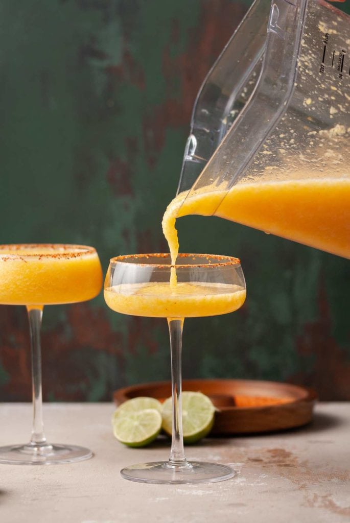 pouring cocktail out of blender and into cocktail glass