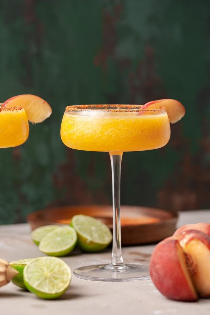cocktail glass with frozen margarita garnished with peach wedge