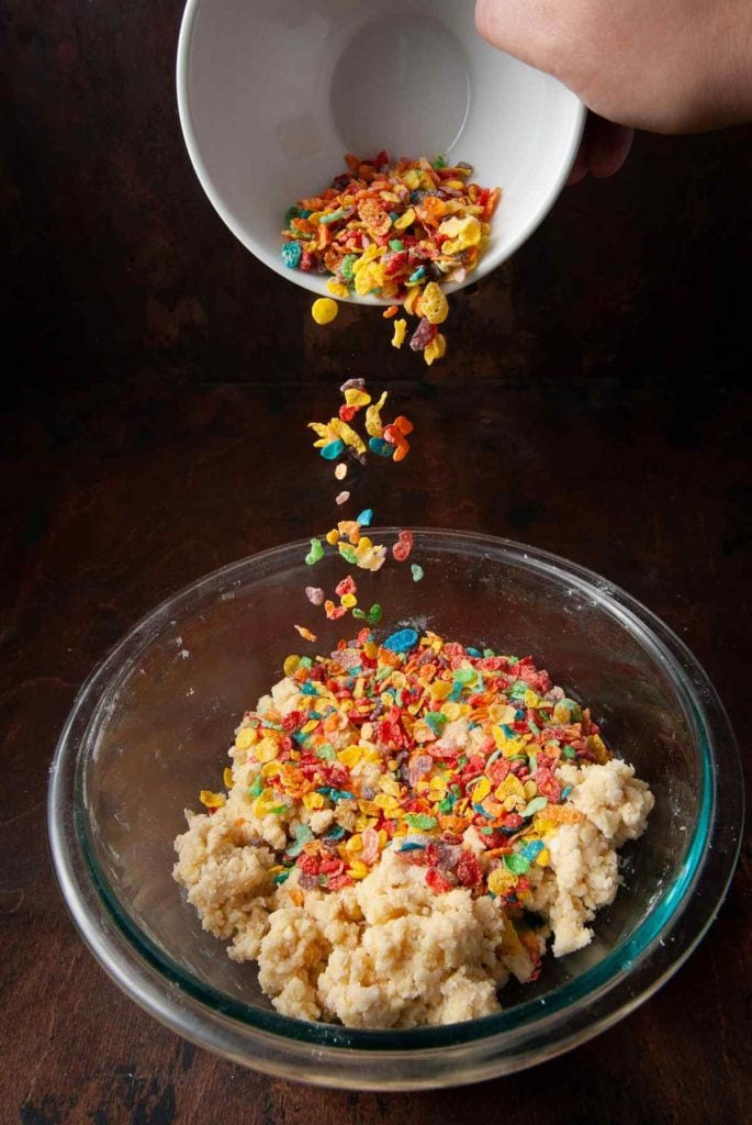 pouring fruity pebbles into cookie dough
