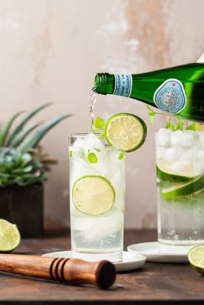 Pouring Sparkling Water into Lime and Mint Cocktail