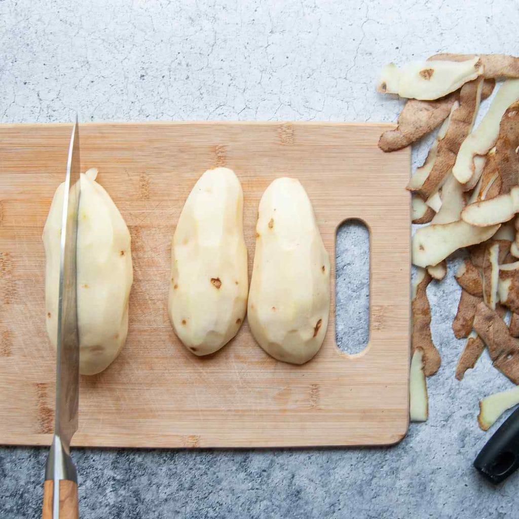 chopping peeled potatoes in half