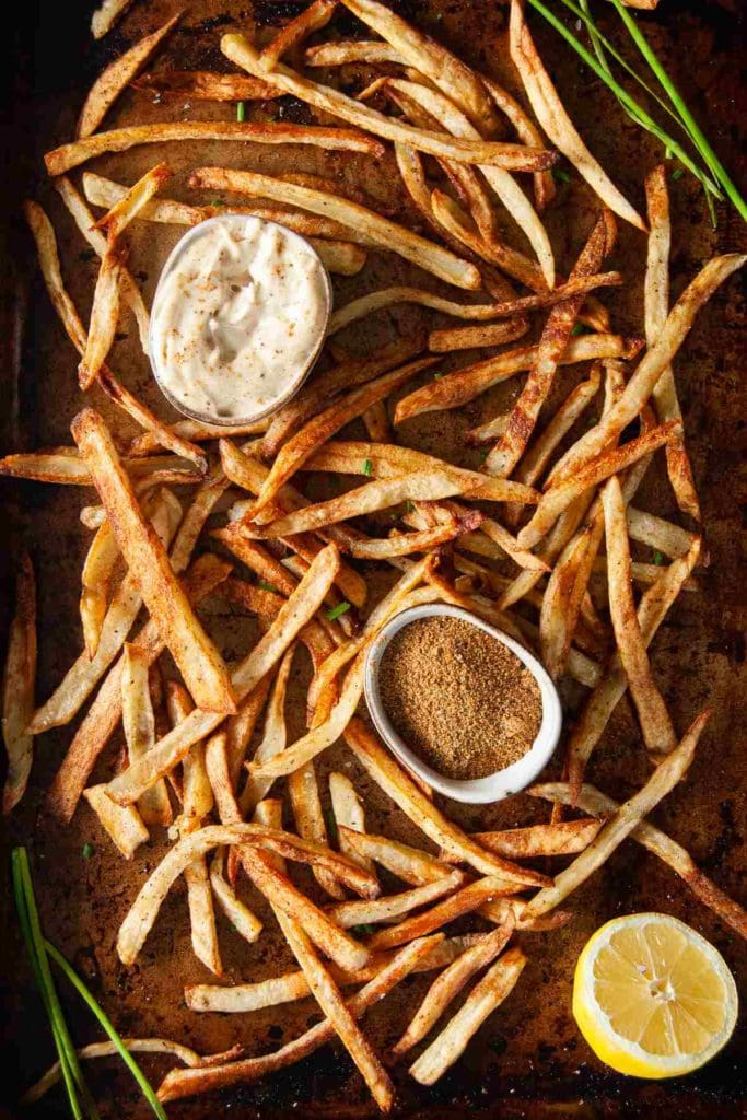 baked golden brown fries on baking sheet with old bay seasoning and old bay aioli
