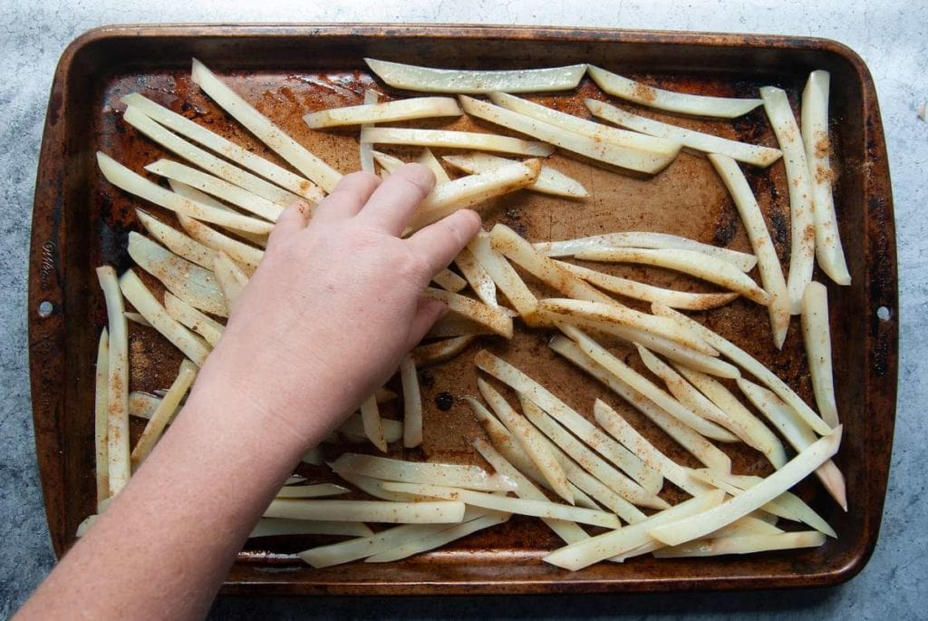 using hands to toss raw french fries