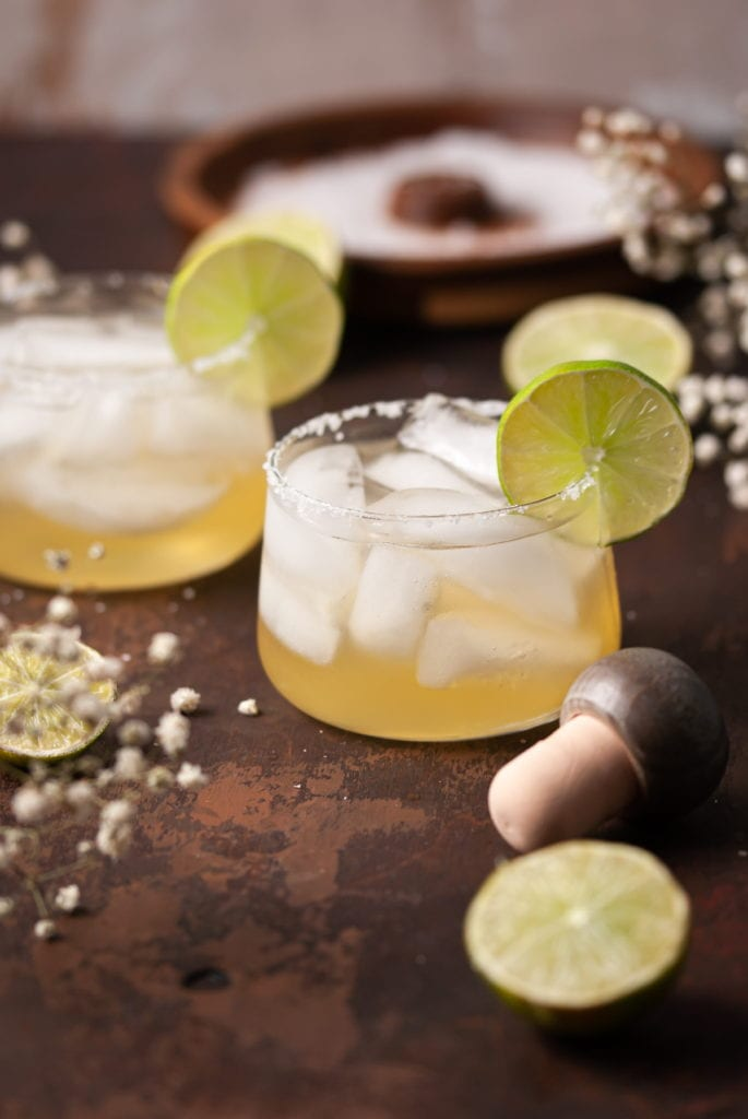 Two Cocktails garnished with lime and a salt rim