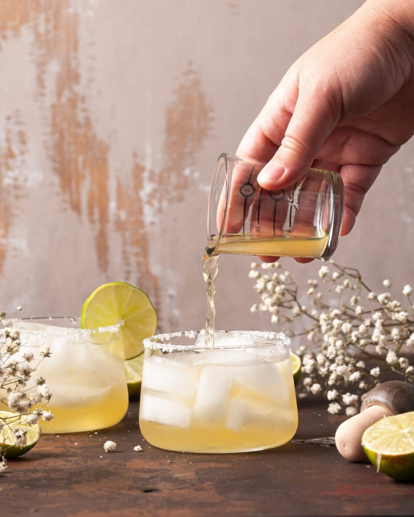 pouring passion fruit juice into margarita