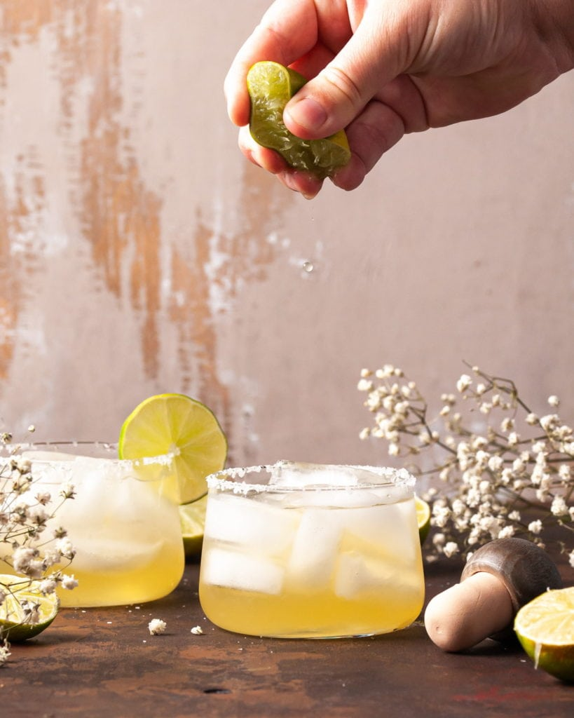 squeezing lime juice into a margarita
