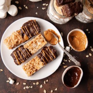 peanut butter rice krispie treats dipped in chocolate and then drizzled with peanut butter