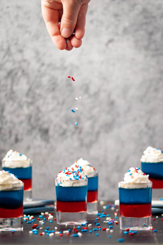 adding patriotic sprinkles on top of whipped cream on jello shots