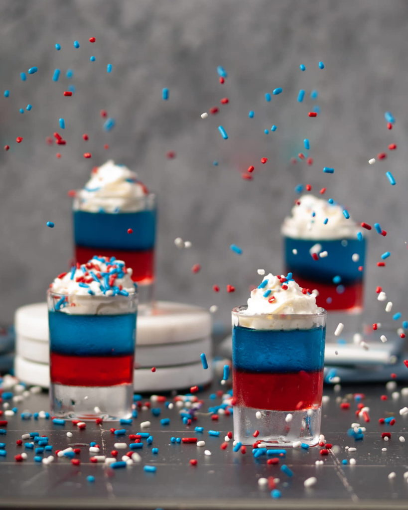 Red White and Blue Jello Shots with Sprinkles Flying in the Air